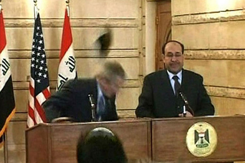 Джордж Буш уворачивается от ботинка, пущенного в него Мунтазаром аль-Зейди. Справа премьер-министр Ирака Нури Аль-Малики